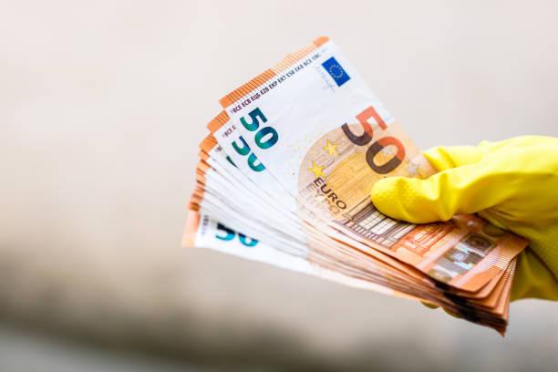 Weltgeldkonzept, Hand mit Handschuhen, die 50-Euro-Banknote erhalten, geben oder halten, isoliert auf verschwommenem Hintergrund. Coronavirus COVID-19 Ausbruch. Konzept der Prävention von Virusausbreitung – Foto