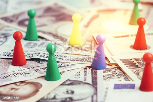 istock World money tariff trade war, colorful plastic game figurines on international major countries banknotes, US dollar, Japanese yen, Euro, Chinese yuan 939841456