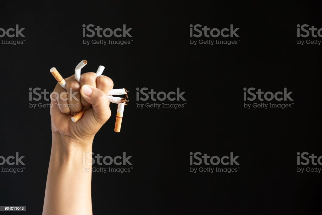 World No Tobacco Day, May 31. STOP Smoking. Close up Man hand crushing and destroying cigarettes on black background. - Royalty-free Abuse Stock Photo