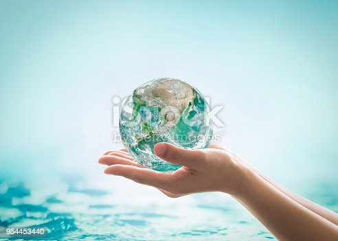 istock World ocean day, saving water campaign, sustainable ecological ecosystems concept with green earth on woman's hands on blue sea background : Element of this image furnished by NASA 954453440