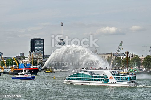 Rotterdam, The Netherlands, September 6, 2019: dredger creating an arch of water, watched by passengers of a Spido tour boat, during the Wereldhavendagen (World Port Days) festival