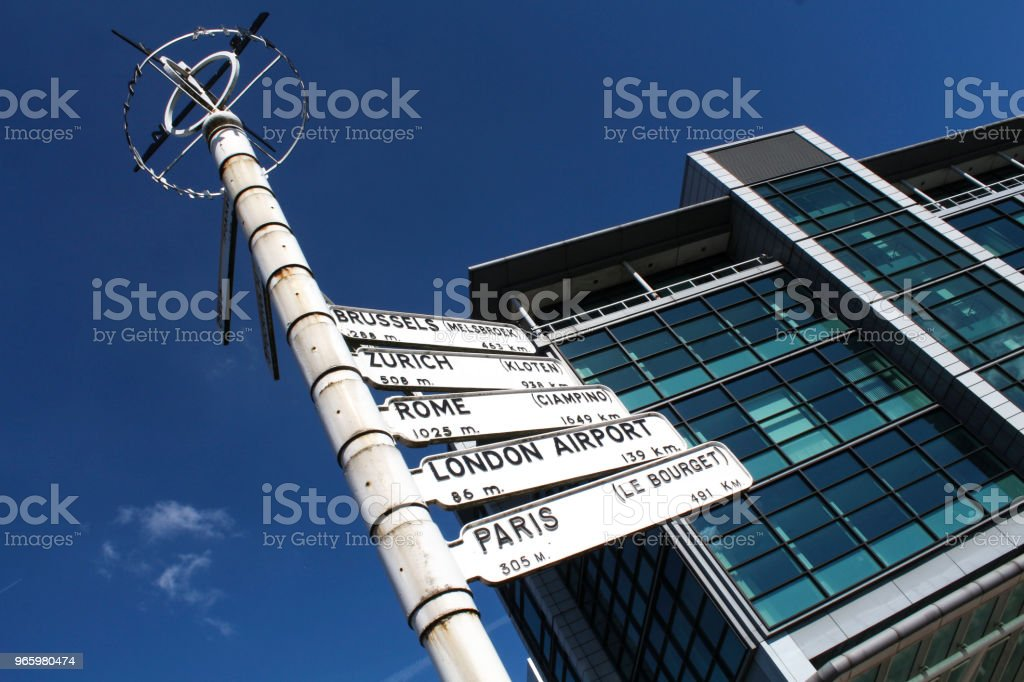 World Sign An arrow sign that points to different parts of the world, shot under a sunny blue sky. Blue Stock Photo