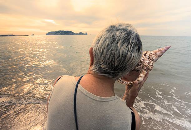 Welt sprechen, ich werde mir anhören Frau mit Muschel am Meer – Foto