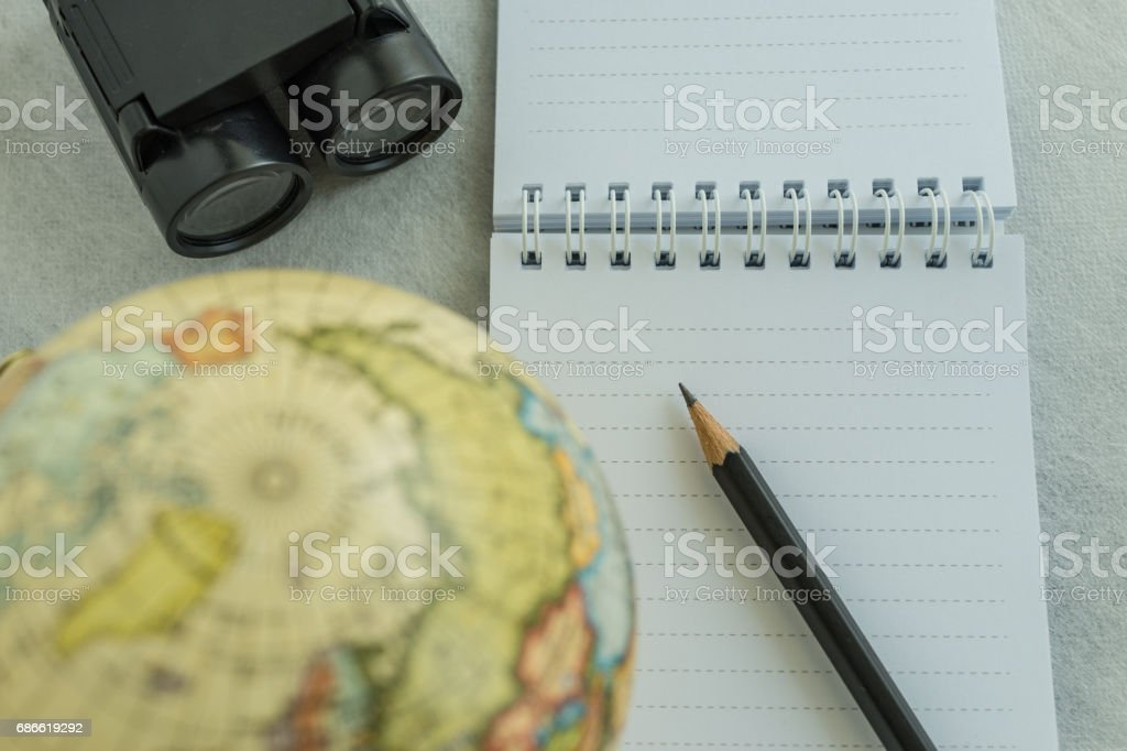 World travel concept with pencil on white note paper, binoculars and small globe on white background royalty-free stock photo