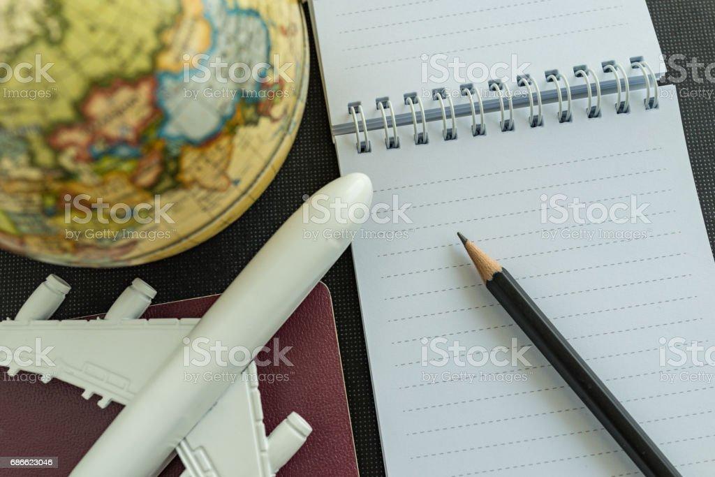 Concept de voyage mondiale avec jouet avion, crayon, passeport, note et globe sur fond noir. photo libre de droits
