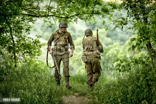 Stock photo of two models dressed as an World War II Army soldiers in an forrest.