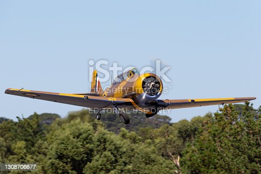 Tyabb, Australia - March 9, 2014: North American T-6 (Noorduyn AT-16) Harvard VH-TXN single engine military training aircraft from World War II taking off from Tyabb Airport.