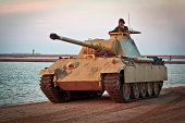 Swinoujscie, Poland - September 14, 2013:Reconstructed in desert camouflage Panther tank with crew drives on the beach in summer sunset, Swinoujscie, Poland.