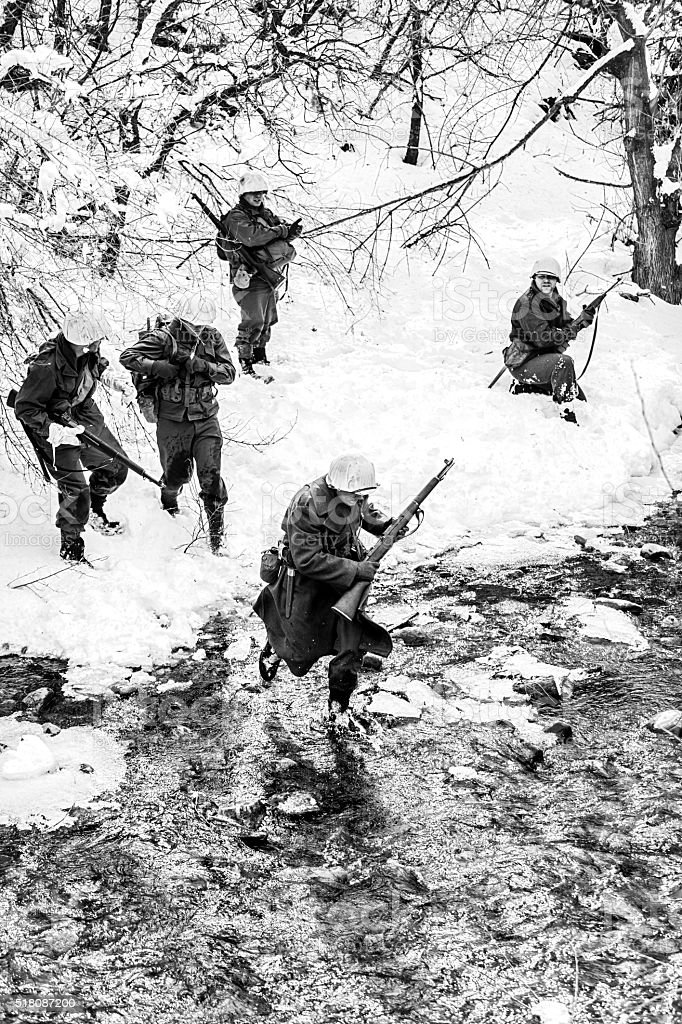 World War II: Soldiers Crossing Creek in the Snow stock photo