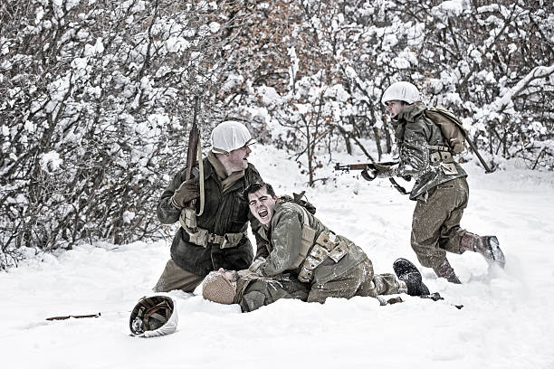 World War II Winter Battlefield Scene With Soldier Down Action shot of US Infantry on the winter battlefield yelling for a medic to help a downed soldier. ambush stock pictures, royalty-free photos & images