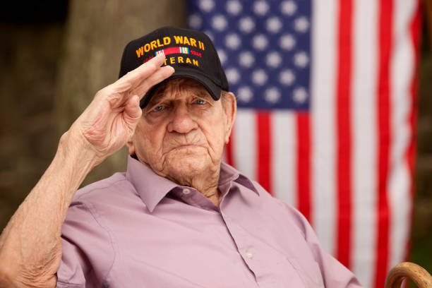 "world war two, veteran wearing baseball cap with text, ""world war two veteran"". saluting - world war ii stock photos and pictures"