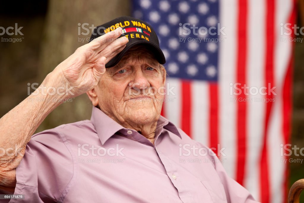 World War Two, Veteran wearing cap with text, 'World War Two Veteran'. Saluting stock photo
