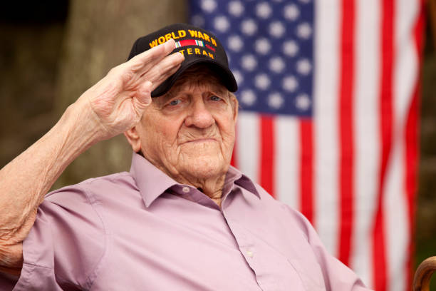 """world war two, veteran wearing cap with text, """"world war two veteran"""". saluting - saluting stock photos and pictures"""
