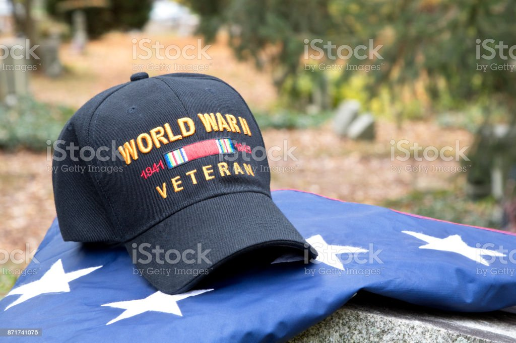 World War Two Veteran's Cap sitting on a tombstone on top of a folded American Flag, stars on flag visible with gravestones in background stock photo