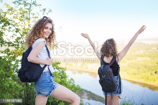 483422527istockphoto A world without borders. Stunning journey of two girls in the mountains. Two girls at the top of the mountain rejoice in a successful ascent. Concept of success and travel 1155167560