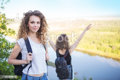 483422527istockphoto A world without borders. Stunning journey of two girls in the mountains. Two girls at the top of the mountain rejoice in a successful ascent. Concept of success and travel 1155399816