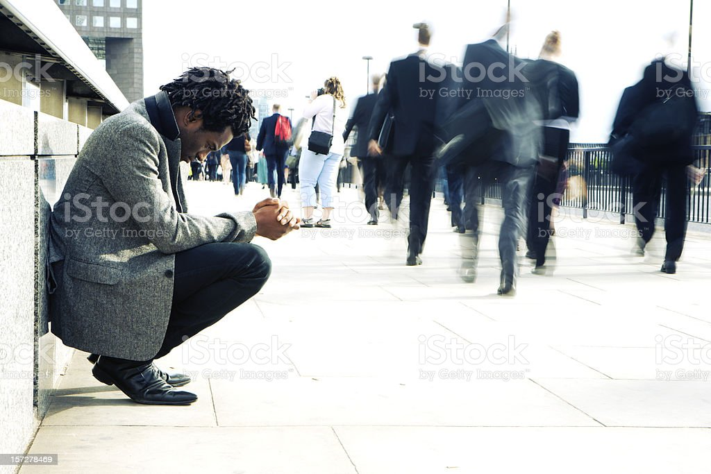 Worlds apart, a man begging the busy streets of London stock photo