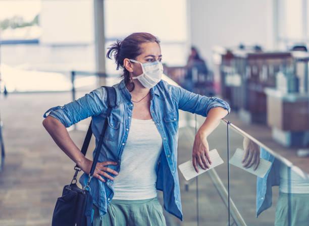 COVID-19 grenzt weltweit an Schließungen. Reisende mit Gesichtsmaske stecken in Flughafenterminal, nachdem die Einreise in andere Länder verweigert. Passagier auf seiner Rückreise ins Heimatland am Flughafen gestrandet. – Foto