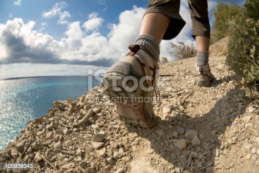 istock Worm's eye view of a hiker on a sunny clifftop trail 105939343