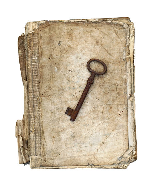 Worn and tattered book and old rusty key stock photo