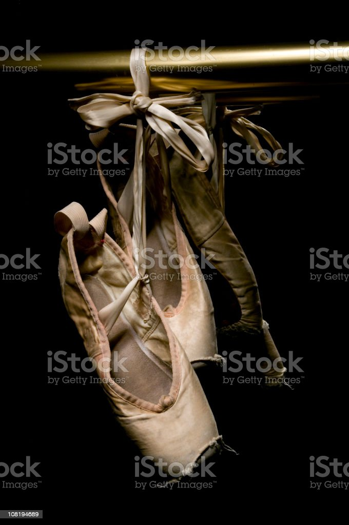 Worn Ballet Shoes Hanging on Brass Rail, Low Key stock photo