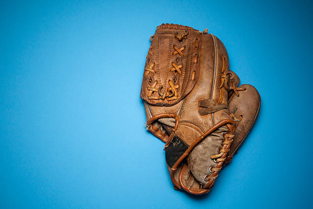 Worn Baseball Glove Againts Blue Background stock photo