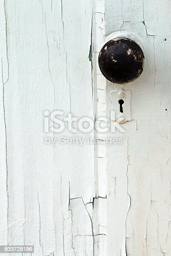 White chipped and painted wood door with knob and key hole.