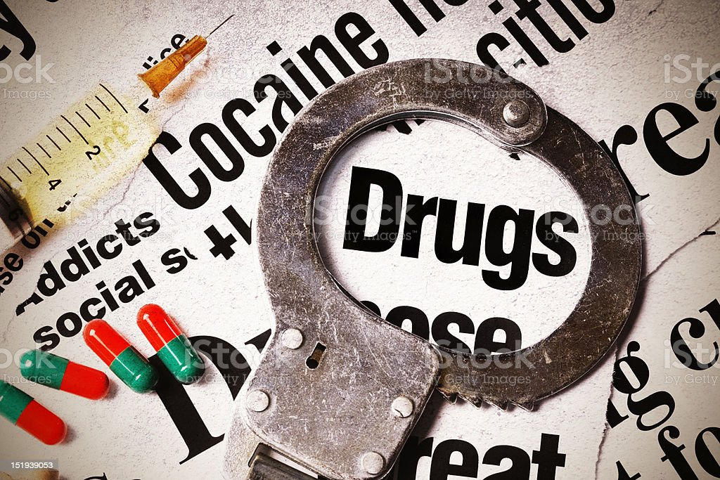Worn handcuff rests on headlines about drugs, pills & syringe royalty-free stock photo