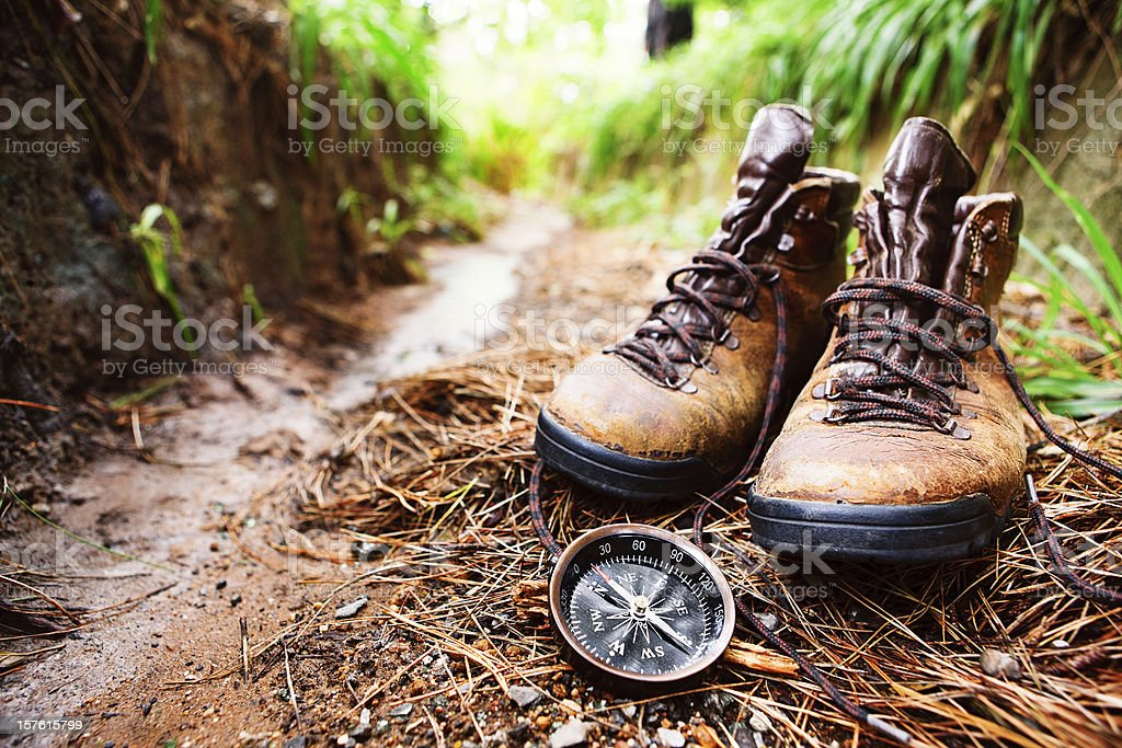 Worn hiking boots and compass on muddy walking trail stock photo