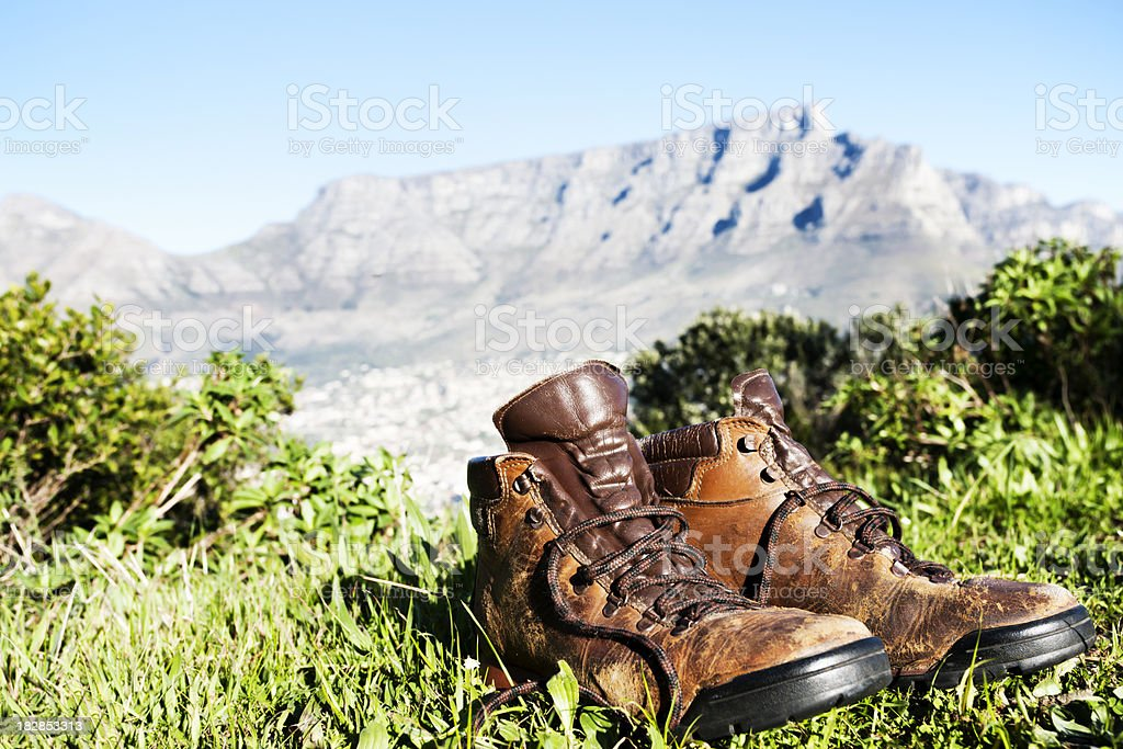 Worn hiking boots with Table Mountain behind them royalty-free stock photo