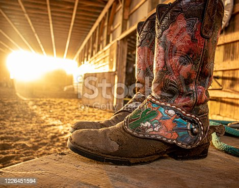 Beautiful shot of some dirty, worn in cowboys boots after a long days work, while the sunset creeps into the barn.
