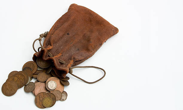 Worn leather purse spilling coins out onto white countertop stock photo