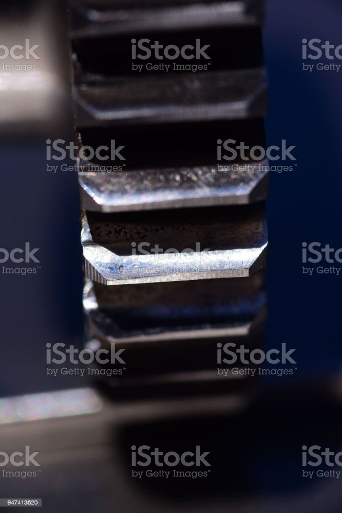 Worn metal on edge of gear teeth due to misalignment of gear on shaft stock photo