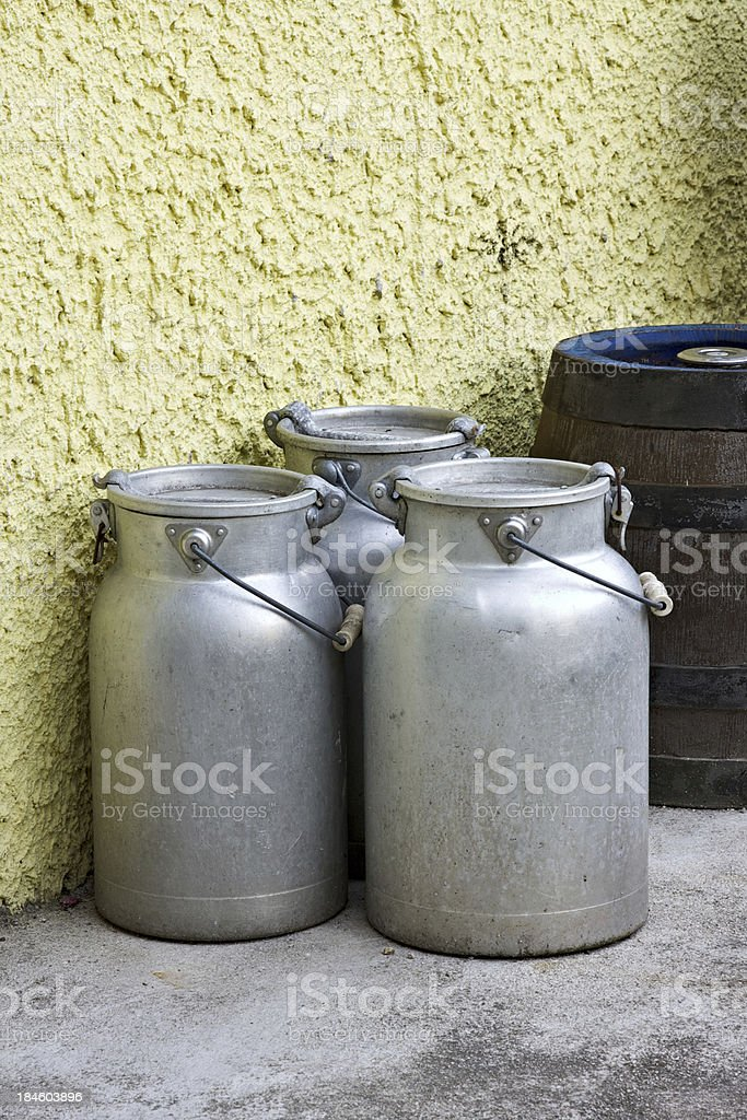 Worn out aluminum bins with fresh milk stock photo