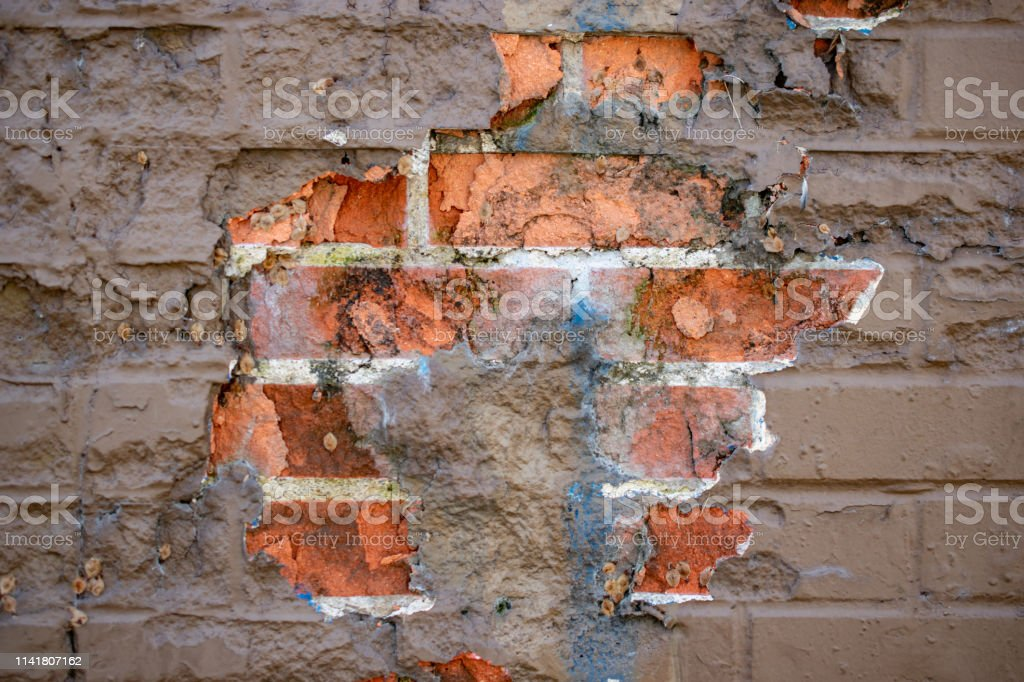 worn painted brick wall with chipped paint stock photo