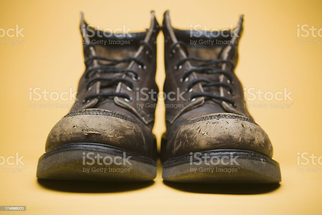 Worn scuffed brown work boots toes on yellow background royalty-free stock photo