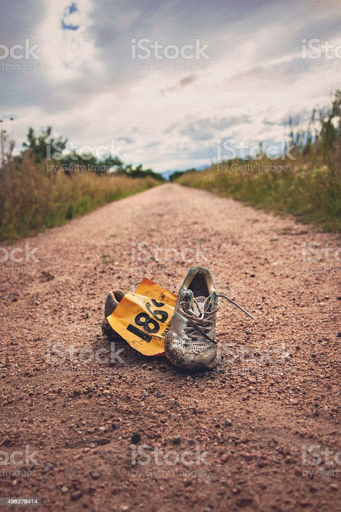 Worn tennis shoes and marathon number discarded after marathon stock photo