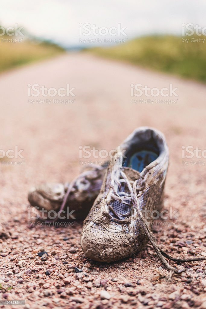 Worn tennis shoes discarded at end of eerie dirt road stock photo