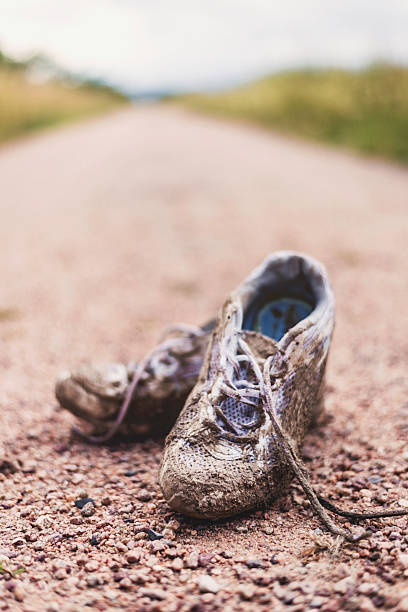 worn tennis shoes discarded at end of eerie dirt road - dirty shoes stock photos and pictures