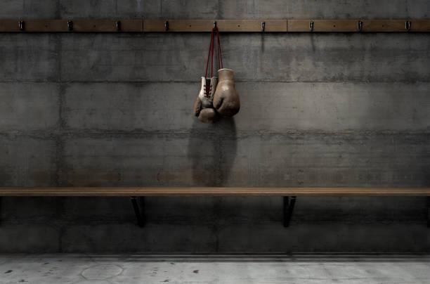 abgenutzte vintage boxhandschuhe hängen in umkleidekabine - bankhaken stock-fotos und bilder