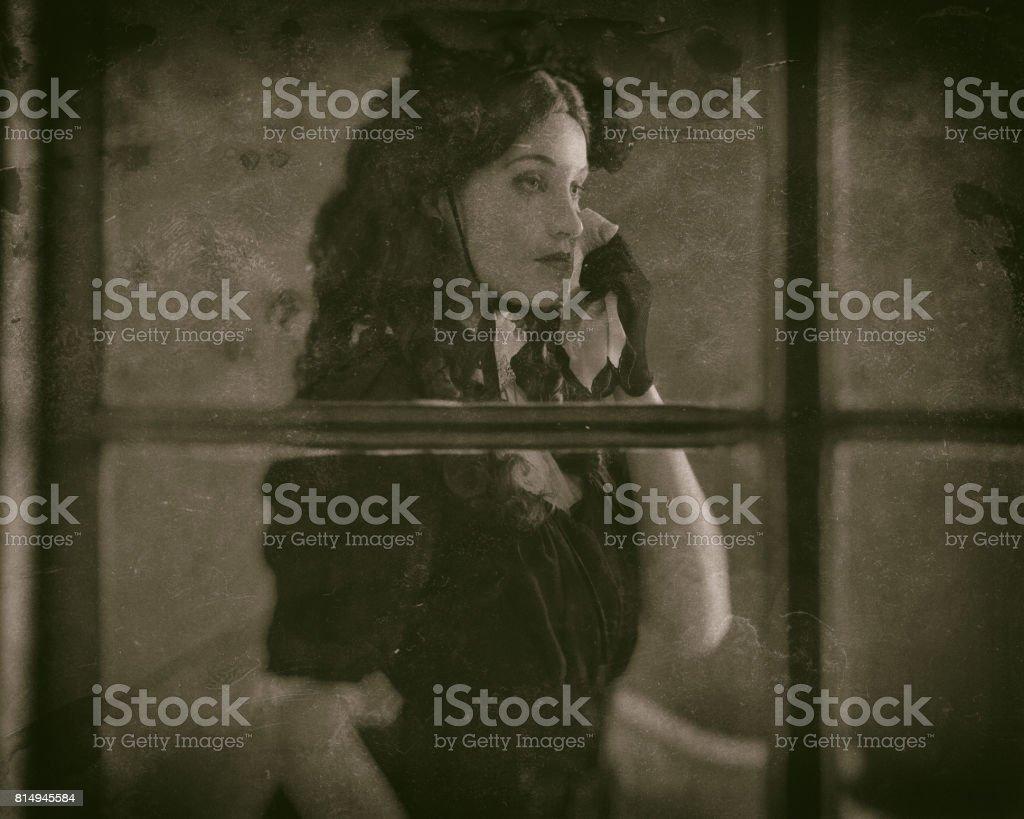 Worn wet plate photo of sad retro victorian woman in black dress...