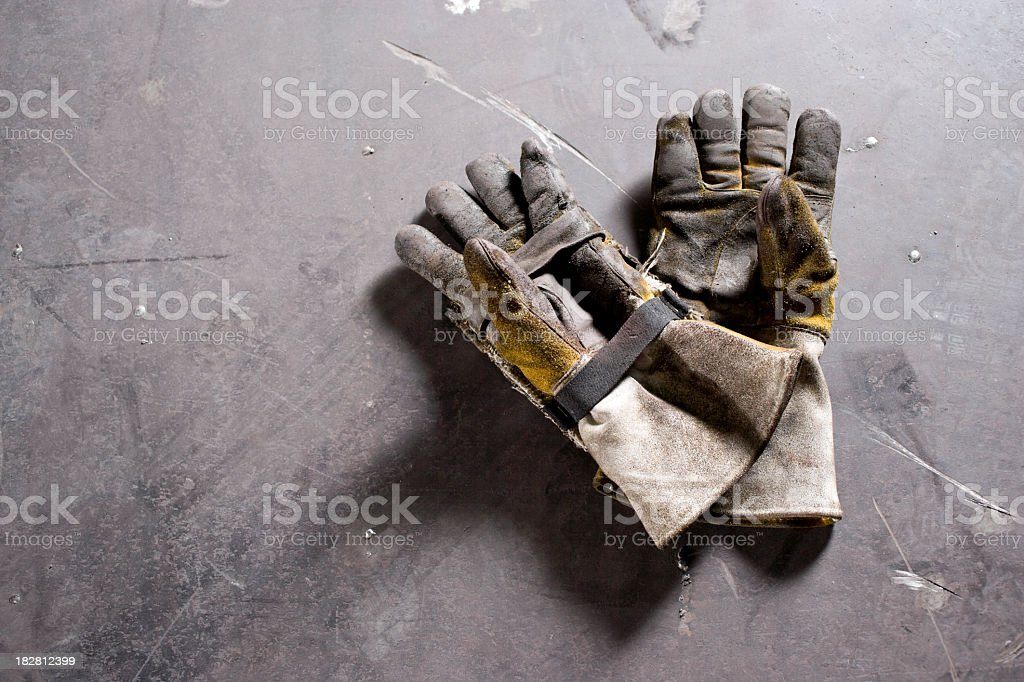 Worn work gloves lying on concrete floor royalty-free stock photo
