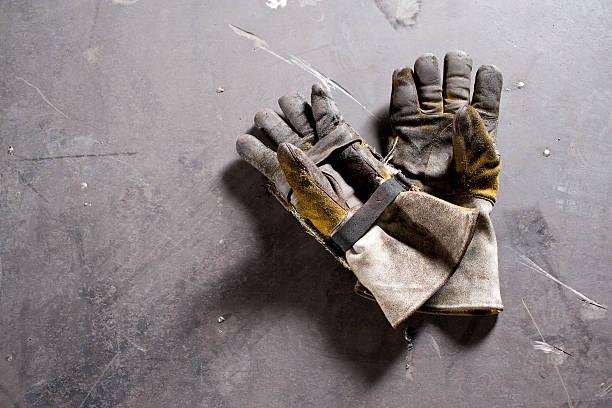 die handschuhe tragen auf beton boden liegen - arbeitshandschuhe stock-fotos und bilder