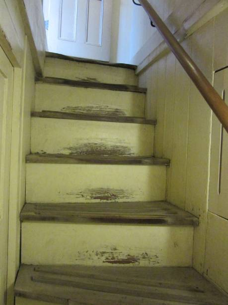 Worn Yellow Staircase Leads to Door in Farmhouse stock photo