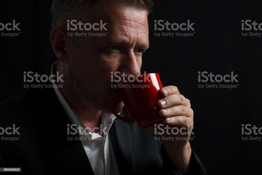 Worried adult man in black suit drinking from coffee cup in front of black curtain zbiór zdjęć royalty-free