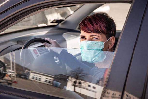 Besorgte erwachsene Frau Fahren zum Shop tragen N95 Gesichtsmaske und Schutzhandschuhe während COVID-19 Ausbruch - Stockfoto – Foto