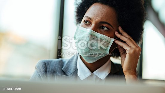 Distraught black businesswoman wearing face mask while being in the office and looking away.