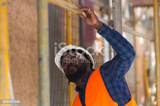 Worried African american engineer looking upwards among scaffolding