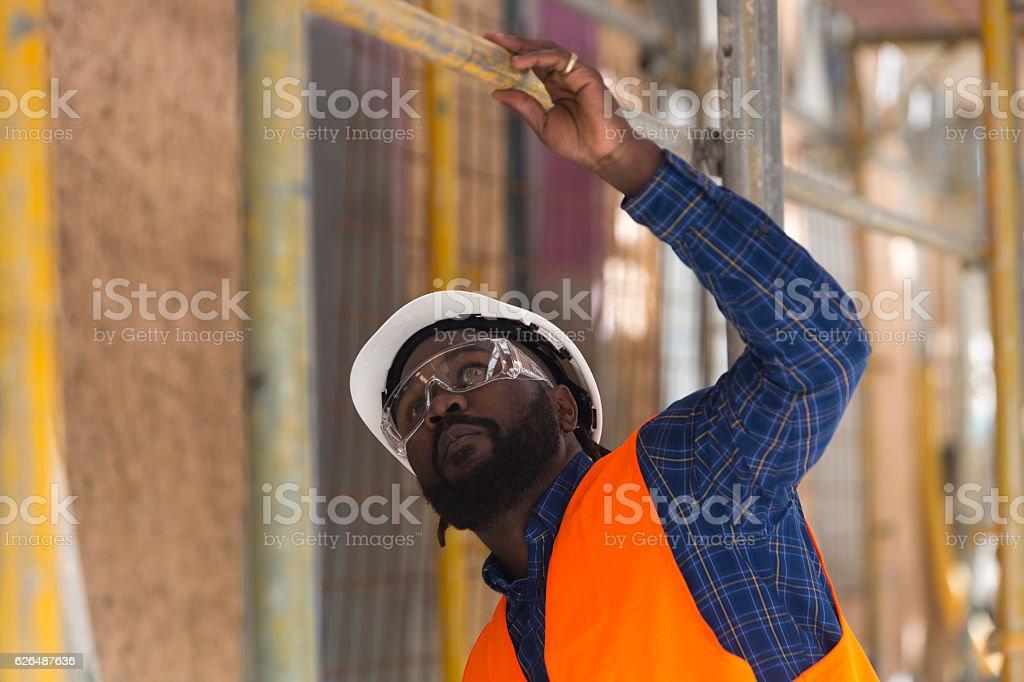 Worried African american engineer looking upwards among scaffolding – Foto