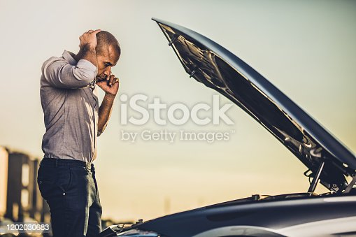 Mid adult black man talking on cell phone while analyzing his car after breakdown on the street.